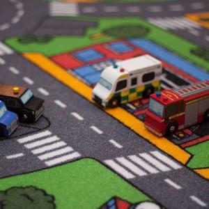 Closeup af Le Toy Van legetøjsbiler på trafiktæppet til biler